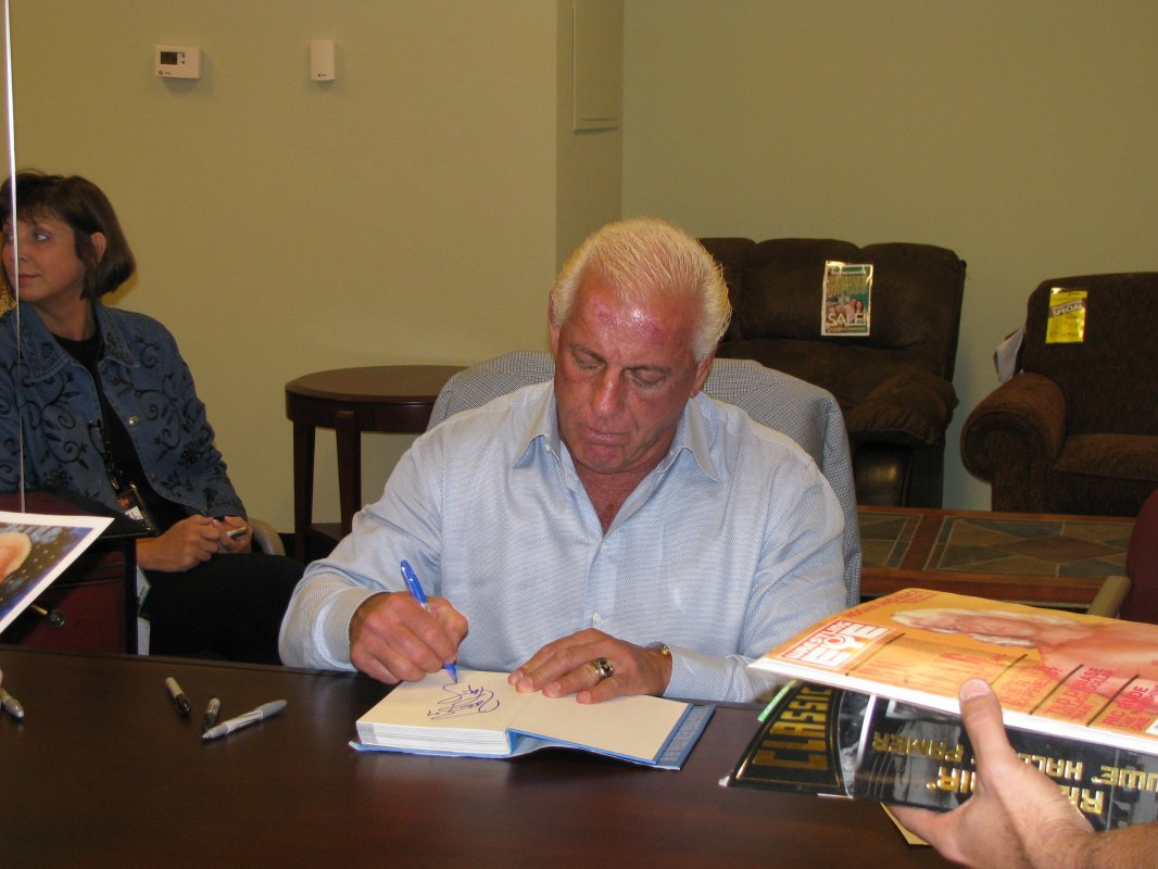 Ric Flair signing a copy of his Autobiography