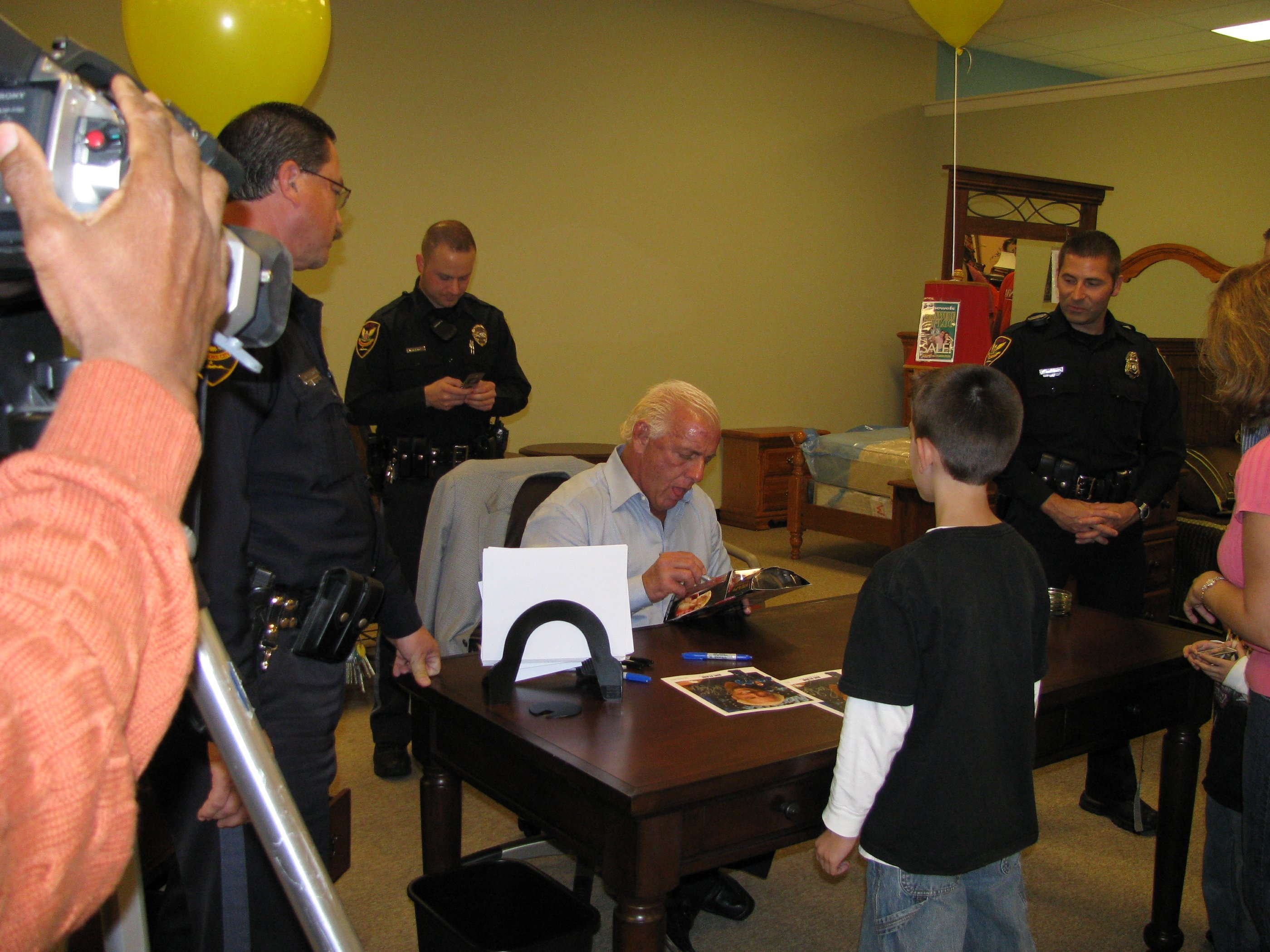 Ric Flair signing a figure of himself for a young boy