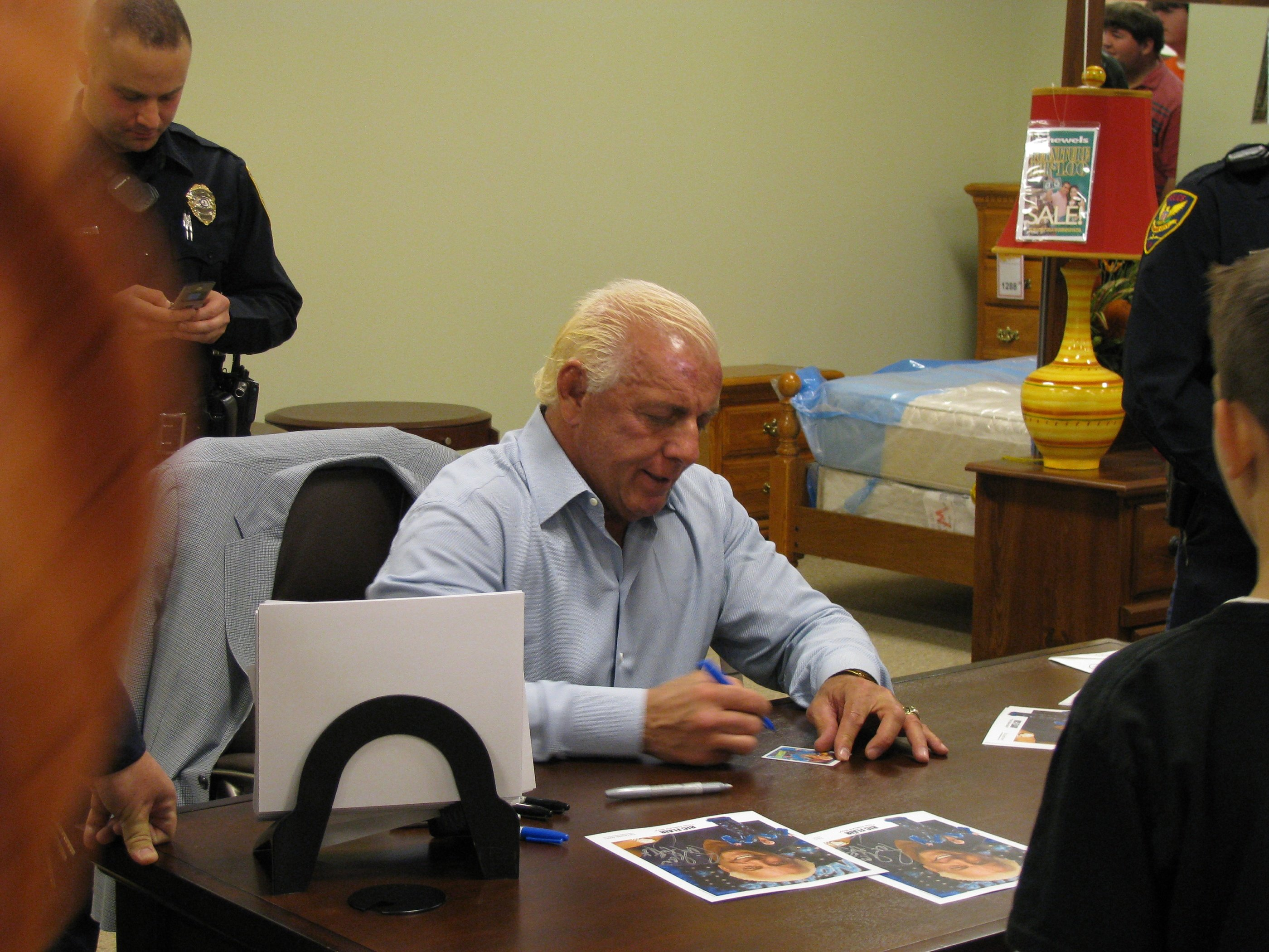 Ric Flair signing a trading card of himself