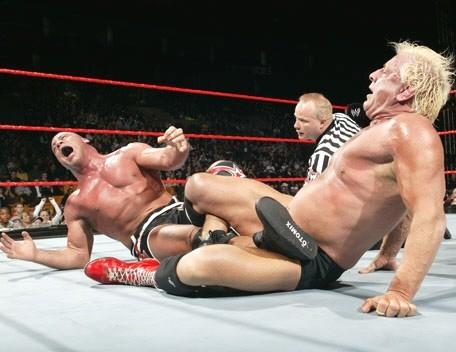 Ric Flair has Kurt Angle in the Figure Four Leglock